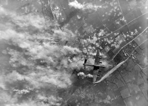Vertical aerial photograph taken during the daylight attack on the German secret weapon (V3) site at Mimoyecques, near Marquise, France, showing a Handley Page Halifax flying over the German positions. June 6, 1944.